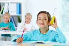 Pupil at lesson. Portrait of cute lad listening to radio while drawing with classmates at lesson Stock Photos