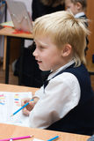 Pupil at the lesson in the classroom. Boy sitting at the desk in the classroom Royalty Free Stock Photo