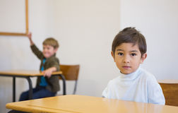 Pupil looking at camera at his desk Stock Photos