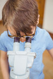 Pupil looking through microscope in class Stock Photography