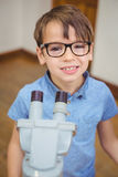 Pupil looking through microscope in class Stock Photo