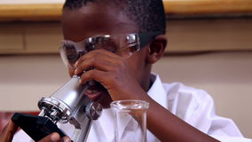 Pupil looking through microscope. At the elementary school stock footage