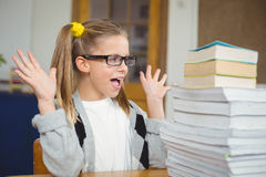 Pupil looking surprised at stack of books on her desk Royalty Free Stock Photography