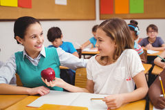 Pupil offering an apple to teacher. At the elementary school Stock Images