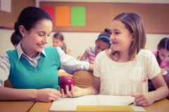 Pupil offering an apple to teacher. At the elementary school Royalty Free Stock Images