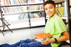 Pupil with pile of books sits on floor in library Royalty Free Stock Image