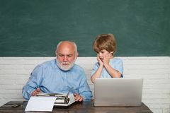 Pupil preparing for test or exam. Man teaches child. Young serious male Pupil studying in school. Portrait of confident royalty free stock photography