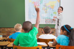 Pupil raising hand in classroom Stock Image