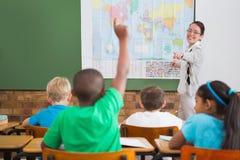 Pupil raising hand in classroom Stock Image