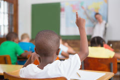 Pupil raising hand in classroom Royalty Free Stock Photos