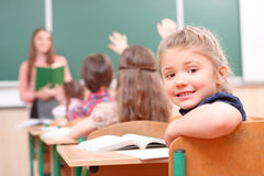 Pupil raising hand turned away from teacher. What is there. Pupil with raised hand turned away from teacher in classroom Stock Photos