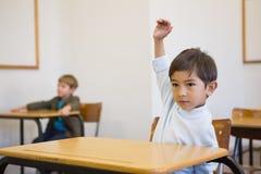 Pupil raising his hand at his desk Stock Photo