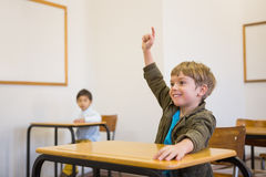 Pupil raising his hand at his desk Stock Photo