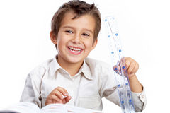 Pupil with a ruler. Portrait of a little schoolboy holding a ruler, looking at camera and smiling stock photos