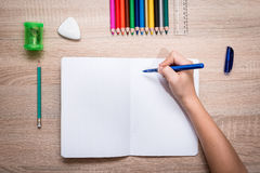 Pupil's desk with akcesories. Blank notebook and hand of child ready to do homework. Flat lay Royalty Free Stock Photography