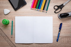 Pupil's desk with akcesories. Pupil's desk with notebook, pencil, crayons, ballpen, scissors, sharpener, rubber on it. Flat lay Royalty Free Stock Images