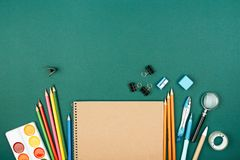Pupil`s desk with stationary. Pupil`s desk with stationary on green background. Preparation to school Royalty Free Stock Photography