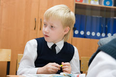 Pupil in school in the classroom. Boy sitting at the desk in the classroom Royalty Free Stock Image