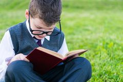 Pupil of the school, sitting on the lawn wearing glasses, and without distraction reading a book royalty free stock photo