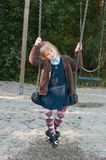 Pupil in school uniform on a swing. Girl in british school uniform sitting on a swing royalty free stock photo