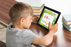 Pupil Solving Math Problem On Digital Tablet. With Stack Of Books On Desk royalty free stock image