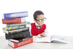 Pupil studying by reading books. Portrait of asian pupil studying by reading books of lessons. shot in studio Stock Photography
