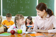 Pupil and teacher. Portrait of smart girl and her teacher looking at each other at lesson in classroom Stock Image