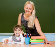 Pupil and teacher in classroom near chalkboard.  Royalty Free Stock Photos