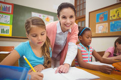 Pupil and teacher at desk in classroom Royalty Free Stock Photo
