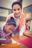 Pupil and teacher at desk in classroom Stock Photography