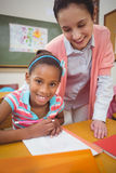 Pupil and teacher at desk in classroom Royalty Free Stock Photography
