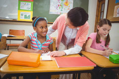 Pupil and teacher at desk in classroom Royalty Free Stock Photos