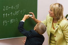 The pupil with the teacher at a mathematics lesson. The schoolboy solves examples at a mathematics lesson Stock Photo