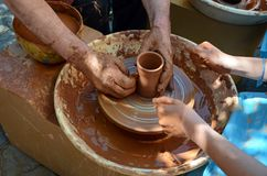 Pupil and teacher of pottery. Potter's hands directed child's hands, to help to work with the ceramics and creating an earthen jar on the ceramic wheel Stock Photo
