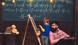 Pupil with teacher at school. Father and son study new knowledge and skills. Kid pointing at chalkboard while hugging royalty free stock photo