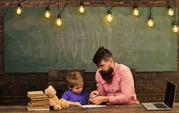 Pupil with teacher at school. Tutor helping kid to write letters in copybook. Man and boy sit at desk with laptop and. Pile of books royalty free stock images