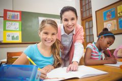 Pupil and teacher smiling at camera during class royalty free stock image