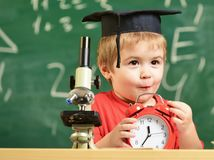 Pupil waiting for school break. Child on excited face looks at alarm clock. School break concept. Kid boy in academic. Cap near microscope, holds clock in stock image
