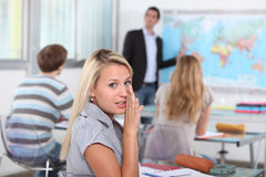 Pupil whispering in class Royalty Free Stock Photo