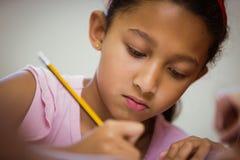 Pupil working hard at desk Stock Images