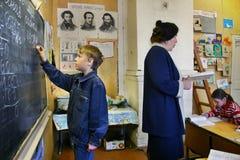 Pupil writes with chalk on school blackboard, classroom rural Ru Stock Photography