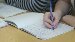 Pupil writes text in a exercise book using a pen. The pupil writes the text in the exercise book using the ball pen stock footage