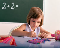 Pupil writing in a classroom Stock Image