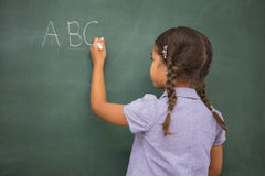 Pupil writing letters on a blackboard Stock Photos