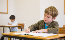 Pupil writing in notepad at his desk Royalty Free Stock Photography