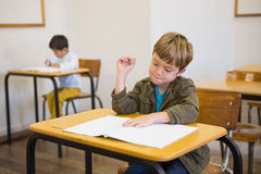 Pupil writing in notepad at his desk Stock Photos