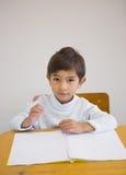 Pupil writing in notepad at his desk smiling at camera Royalty Free Stock Photo