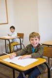Pupil writing in notepad at his desk smiling at camera Royalty Free Stock Photos