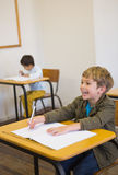 Pupil writing in notepad at his desk smiling Stock Image