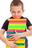 Pupila con la pila enorme de libros Imagenes de archivo